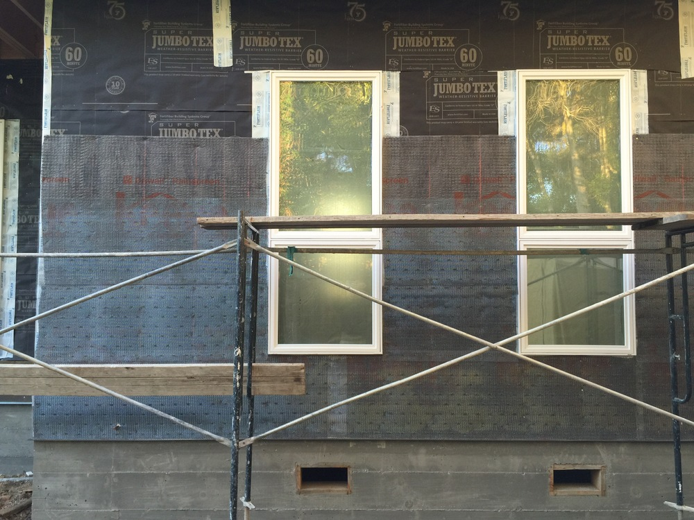 A rainscreen was applied over the (black) building paper to hold the siding off the wall in case any moisture builds up and for vapor to breath. On top of the rainscreen, was attached the wire mesh to hold the scratch coat. You can see it going up here.
