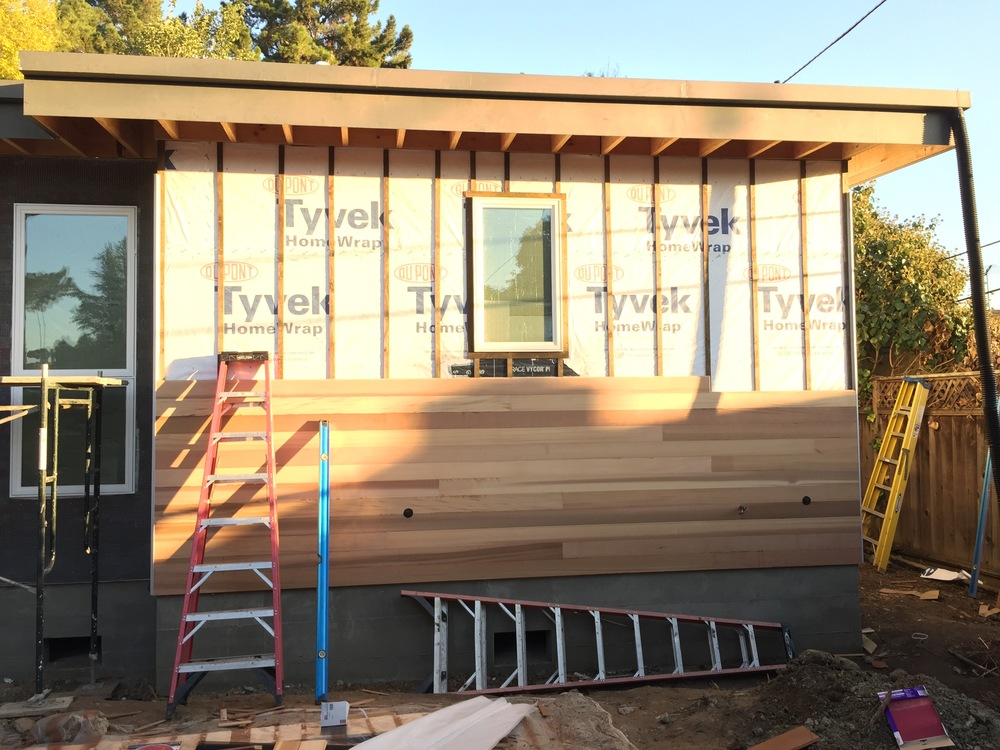 The back-sealed cedar pieces make their way up onto the wall itself. The strips of furring hold the cedar away from the actual building paper so everything can breath. The cedar finish you see here is still natural. The finish stain is applied after all the wood siding goes up.
