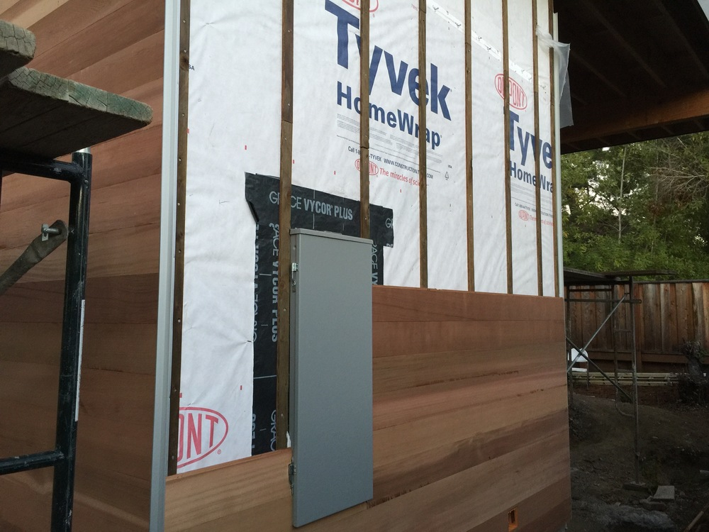"""Our contractor suggested we use an """"X"""" corner bracket at the outside corners. The metal strip at the corner caps the wood siding and it turned out super nice. Notice the building paper, and vycor. The wall breathes, but we don't want moisture to get inside the house."""