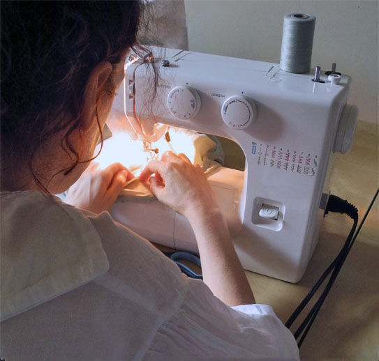 Folding fabric as it passes under the needle