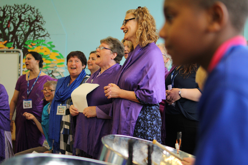 Sacred Sounds Women's Choir performing alongside the steel band at Gorton Mount Primary Academy at an event celebrating World Music Day Photo: Mark Thomas for Manchester International Festival