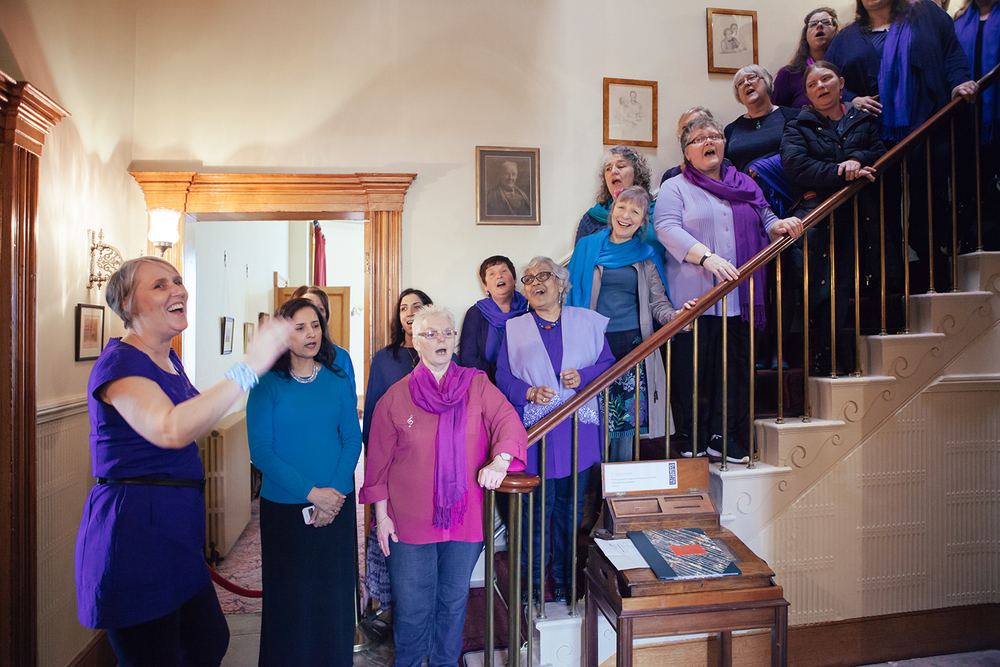 Sacred Sounds Women's Choir perform on the staircase at Elizabeth Gaskell's House in celebration of International Women's Day 2016