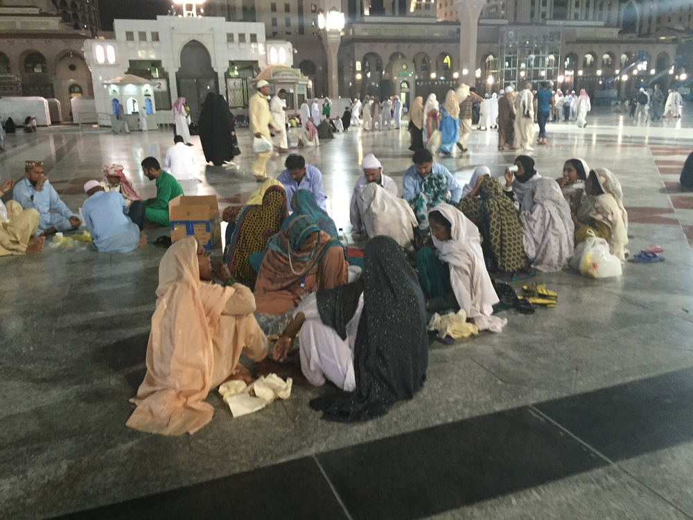 Pakistani pilgrims picnicing with the mosque as a backdrop