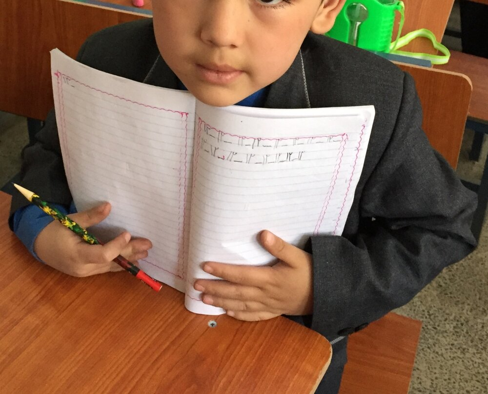 Student from AFN Pen Pal School showing off his penmanship