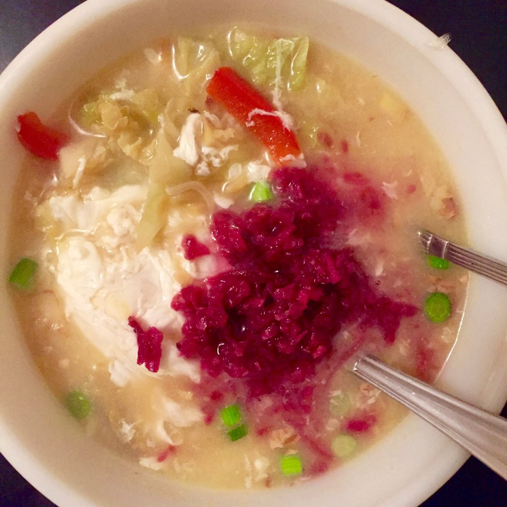Simple miso ginger chicken broth with veggies, a poached egg for protein, pink sauerkraut, and scallions.