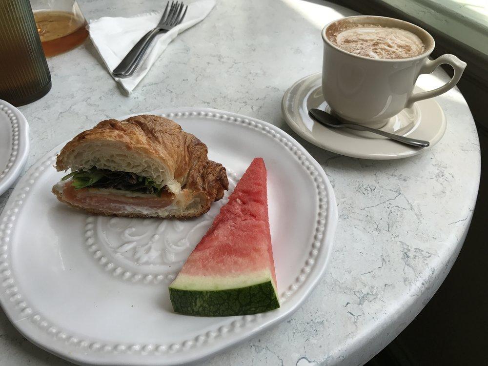 Atlantic sandwich on croissant with fresh watermelon and a macchiato.