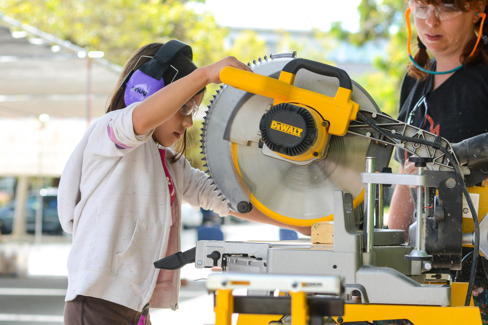 Young girl using a chop saw