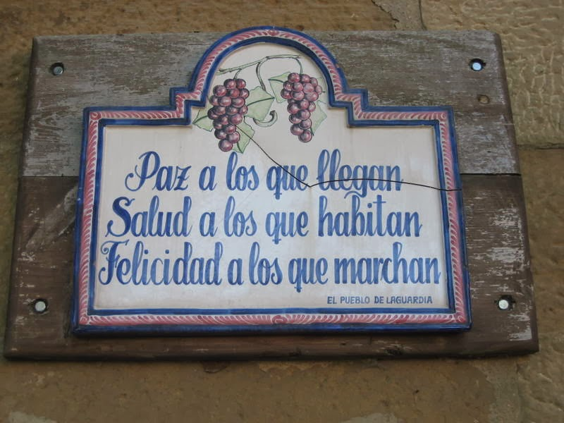 "Plaque at one of the medieval gate entrances into the walled city of Laguardia: ""Peace to those who arrive, Health to those who live here, and Happiness to those who depart"""