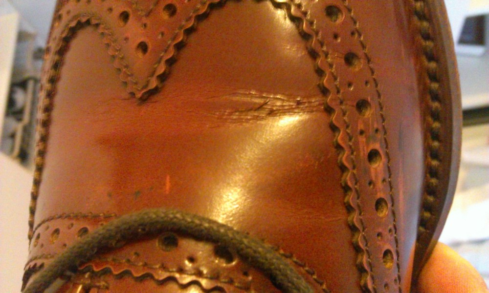 Corrected grain leather usually show cracks on the surface of the leather rather than gentle creases.