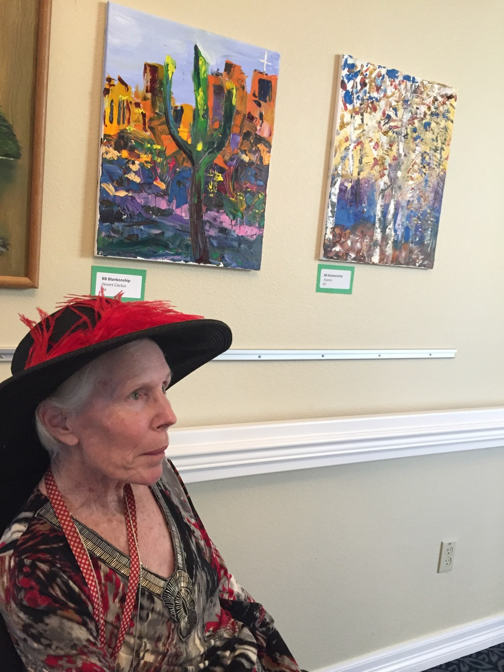 Mom in front of one of her paintings at an art exhibit