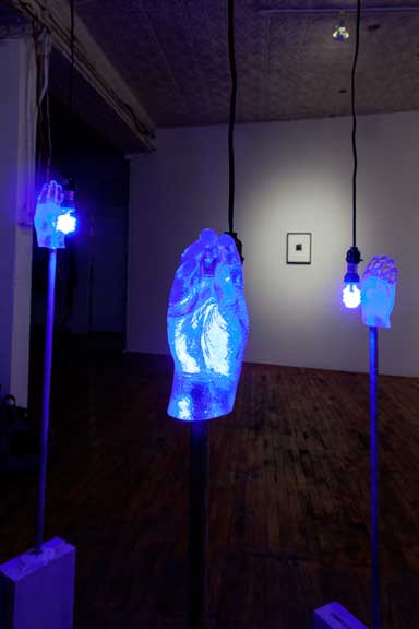 Ivan LOZANO,   MILAGROS I, MILAGROS II, and MILAGROS III,   2012. Resin cast of surgically reconstructed hand, metal pipe, silicone caulk, cinderblock, paint, UV light bulb. Dimensions variable.