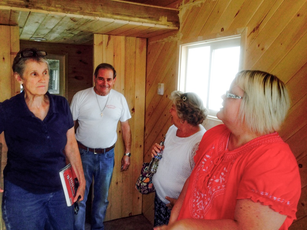 Local contractor and volunteer mission builder Mike Robinson displays the Tiny House interior for representatives of non-profit organizations.