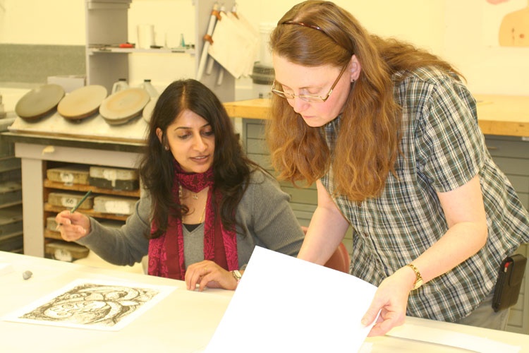 Archana Shekara signing prints. (Photo by ISU College of Fine Arts)