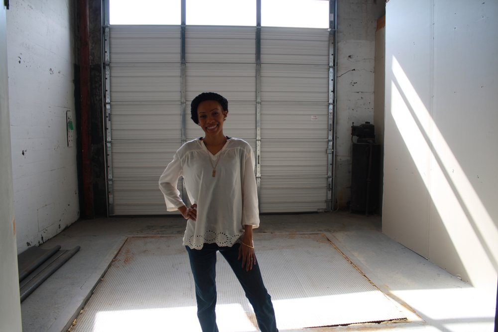 Yasmeen is shown standing inside the loading dock of the space for her food hub, which is designed to store and develop food products for last mile distribution