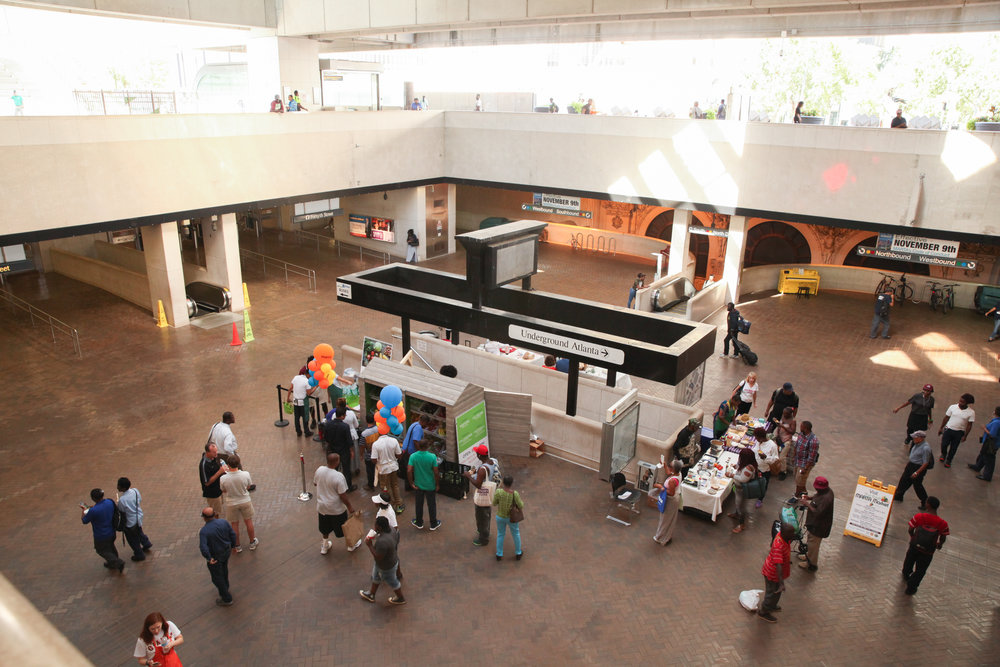Patrons visit a Fresh MARTA Market stand featuring fresh produce inside a MARTA station