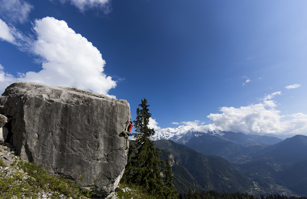 Tommy Caldwell bouldering with the Mont Blanc Massif behind.