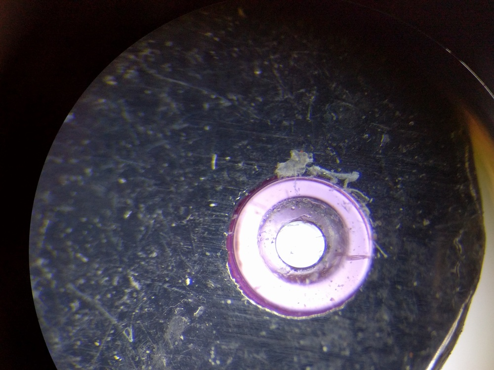"This is one of the ruby bearings found in the assembly, approximately 0.05"" in diameter."