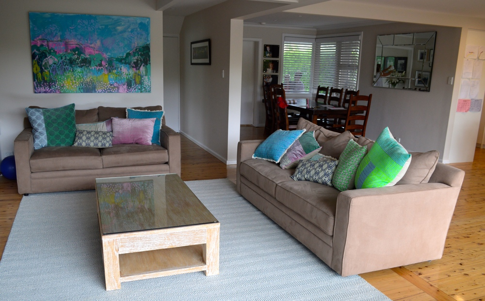 Living area with new artwork, cushions, rug & coffee table