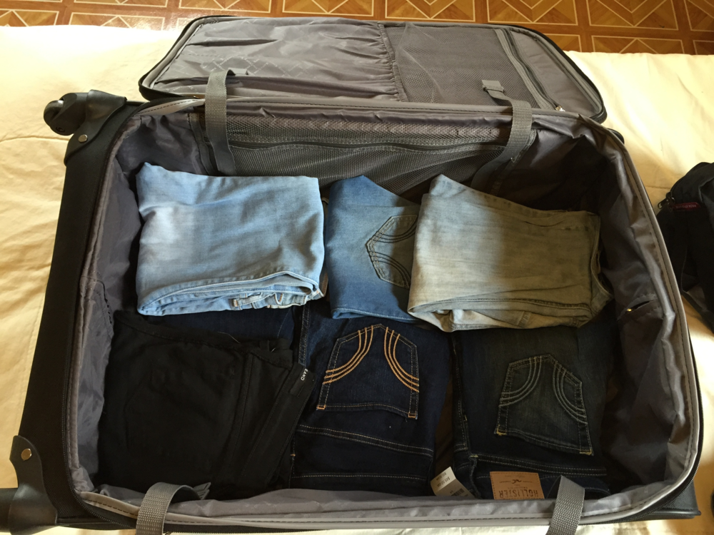 Jean arranged at the base of the suitcase