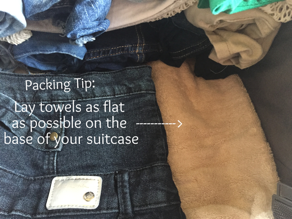 Lay towels as flat as possible on the base of your suitcase