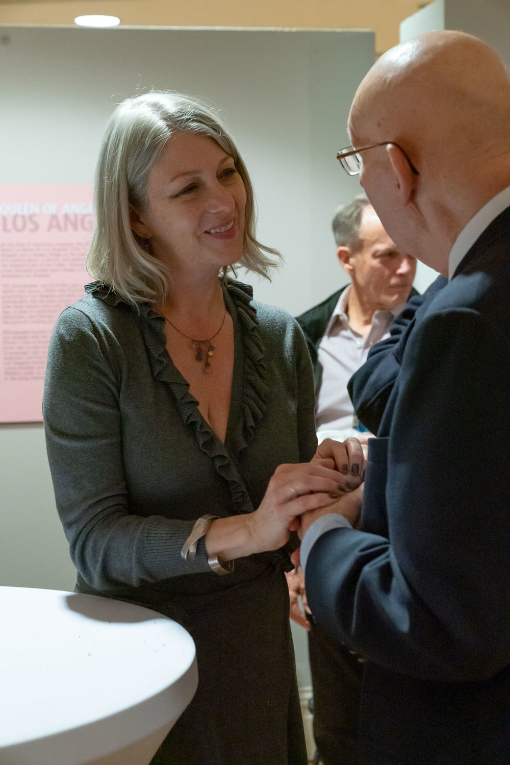 """Historian Anthea M. Hartig greets patrons at the opening of """"Boomtowns: How Photography Shaped Los Angeles and San Francisco."""""""