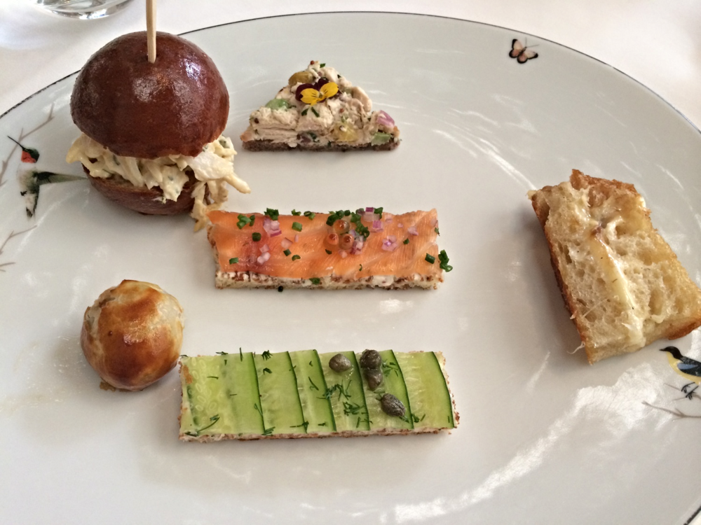 Clockwise from top left: Crab roll on brioche, smoked salmon toast with salmon roe, chicken salad with edible flowers, truffled grilled cheese, cucumber and caper toast, warm mushroom duxelle