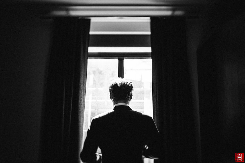 028-groom-tilt-shift-getting-ready-portrait-window-drama.jpg