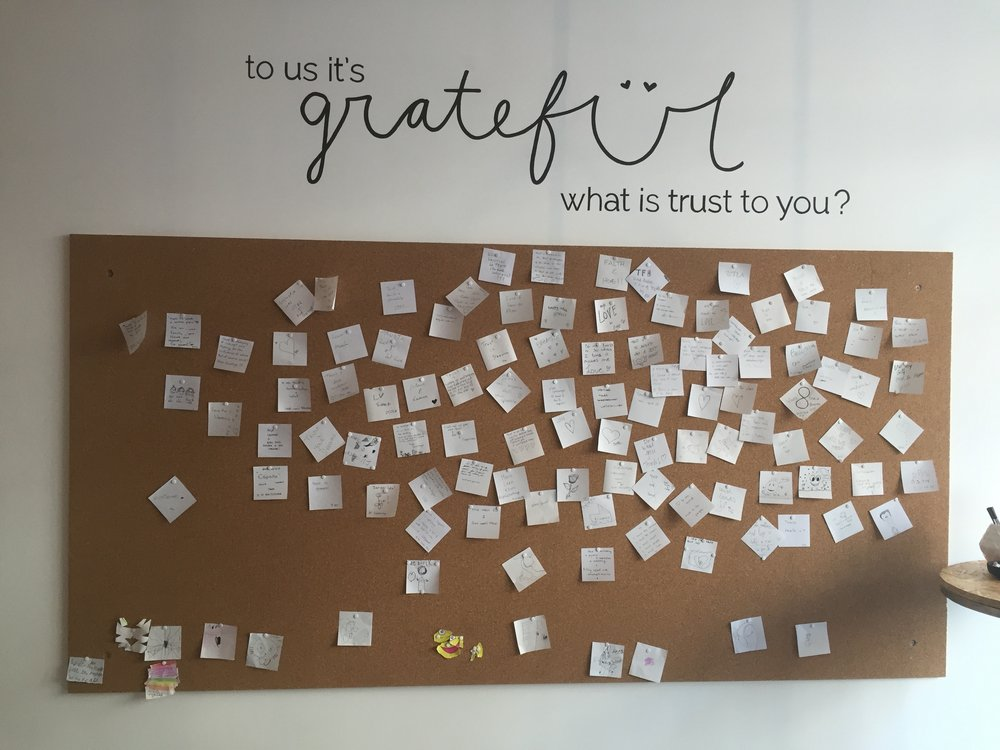 A gratitude wall in the shop, celebrating trust.