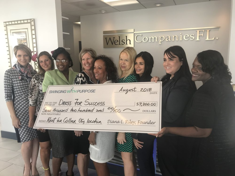 Diana Riley of Swinging With a Purpose is presenting a check to Dress for Success SW Florida with the WETES graduates and volunteers at Welch Companies of Florida