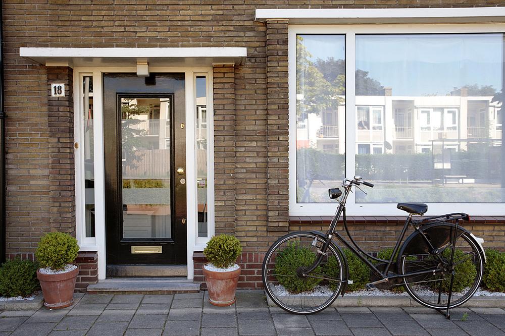 Front domu: olbrzymie okno i amsterdamska zieleń na drzwiach