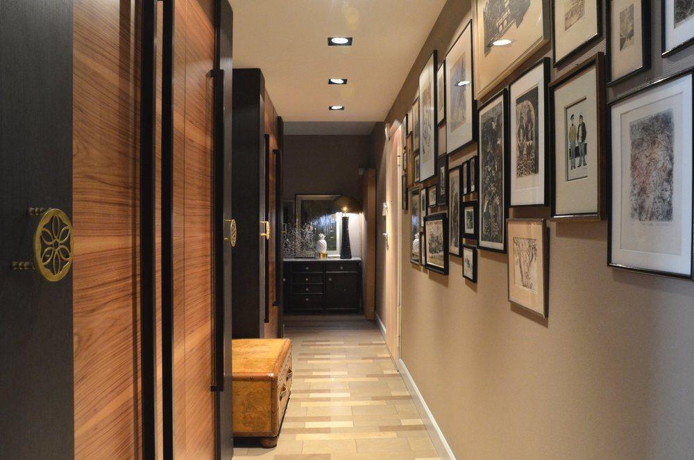 Długi korytarz z szafami oraz kolekcją grafik
