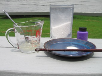 Step 1: Measuring cup with dissolved sodium alginate, note viscous drop on end of chopstick; dry sodium alginate powder on blue saucer; package of calcium chloride (for step 2) and purple Kid's Paint bottle (step 3 ) in background.