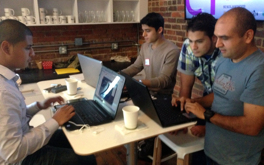 Ramiro works with Marcel, Ruben and Jorge as they code the first version of the new app.