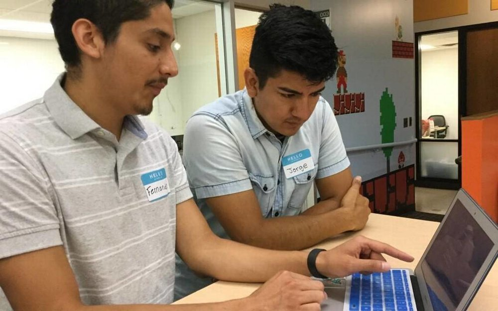 Fernando Osorto, left, and Jorge Rodriguez discuss an app they developed for Student Action with Farmworkers through the Code the Dream project sponsored by Uniting NC. Osorto and Rodriguez spoke at Code the Dream classes on July 29, 2017, at the American Underground in Durham, NC.