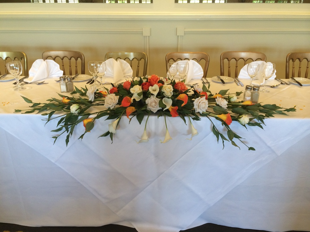Top Table Display - With Ivory & Orange Calla Lilies, Ivory & Orange Roses With Greenery