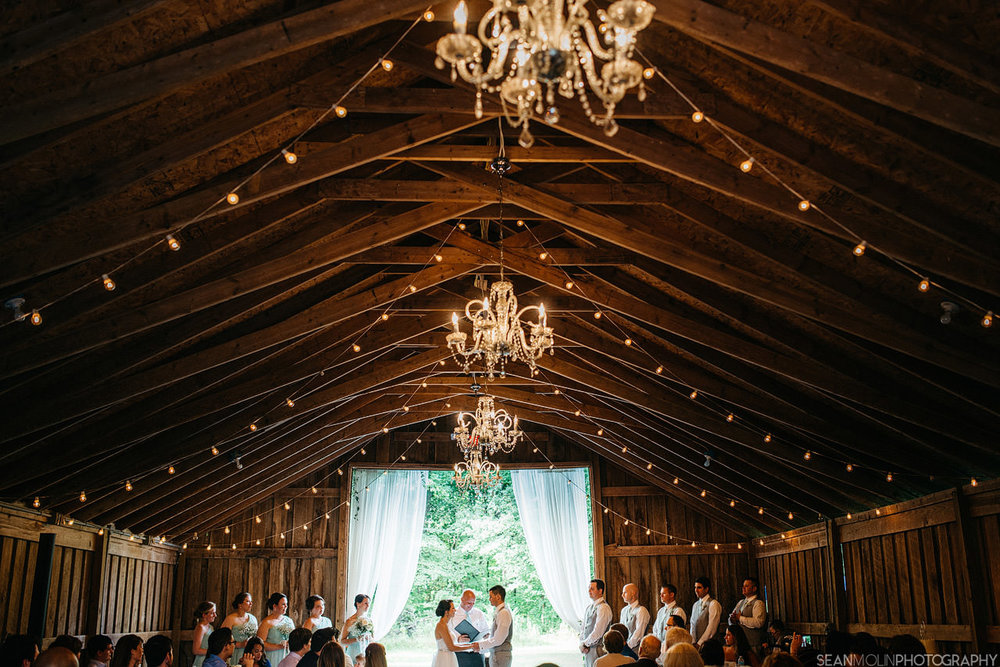 057-barn-zionsville-indiana-wedding-jessica-eric-uhlir-ceremony-chandelier-wide-angle.jpg