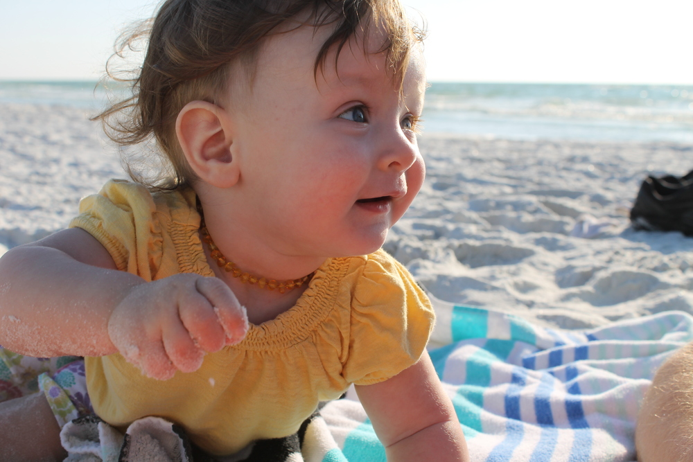 baby with sand at the beach