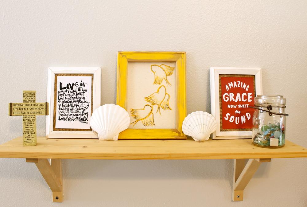 natural wood IKEA shelf, thrift store frames and art prints