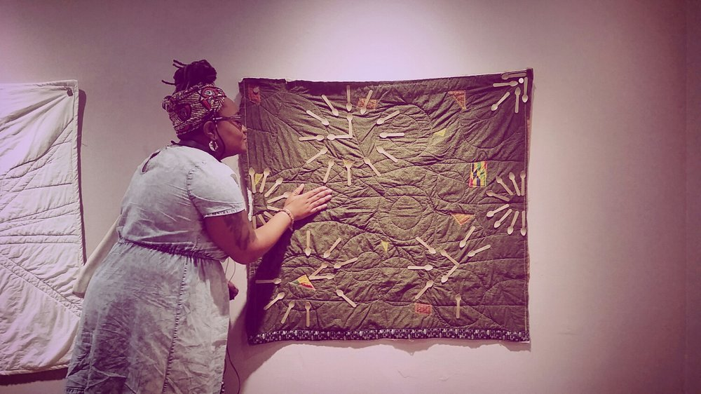 [image: a gallery interior. A green/patchwork quilt w wooden spoons hangs on a grey-purple wall. A black spoonie wearing a denim dress and colourful headwrap leans in and places a hand on the quilt and gives it a kissy face.]