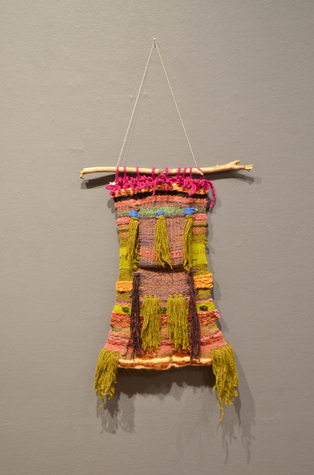 Self-Portrait #2 (as ancestor) wood, wool, cotton. 2016.  Image Description: Woven wool tapestry hanging from fucsia loops on a wood branch against a gray-pink wall. Interwoven horizontal bands of pink, green, purple, gold, brown with blue and peach accents. Green and burgundy tassels hang from center and bottom.
