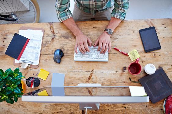 Man writing on keyboard at his desk