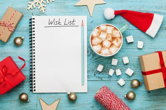 "A blank page labeled ""Wish List"" surrounded by presents, hot cocoa, bells, and a Santa hat"