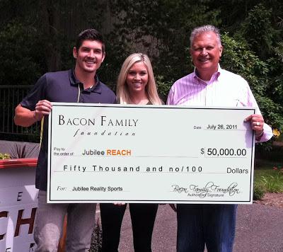Tony Bacon & Ali Bacon present a check to Jubilee Reach Executive Director Brent Christie