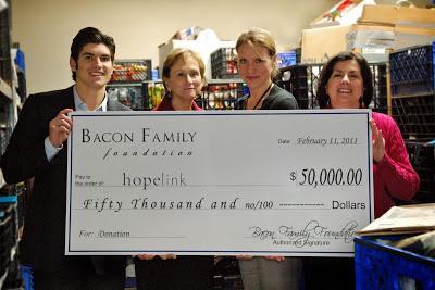 Tony Bacon from The Bacon Family Foundation presents a check to Hopelink CEO