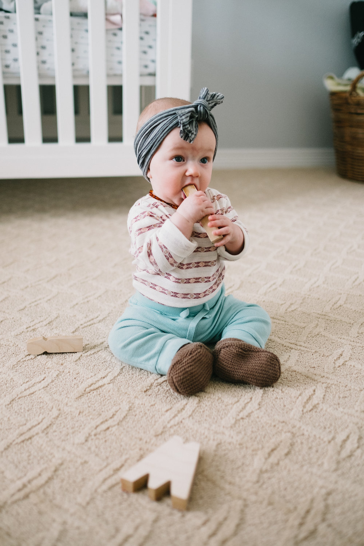 Baby on floor chewing on block