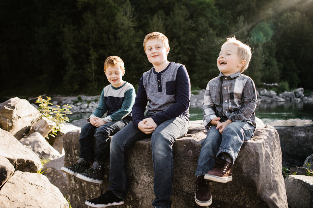 Three young brothers laughing on rock