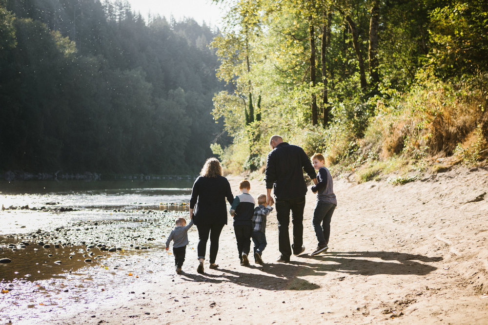 Family of six walking by river