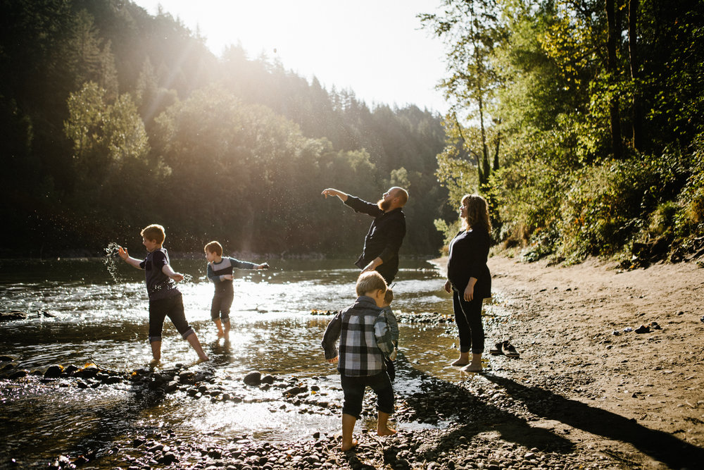 Young family of six throwing rocks in river