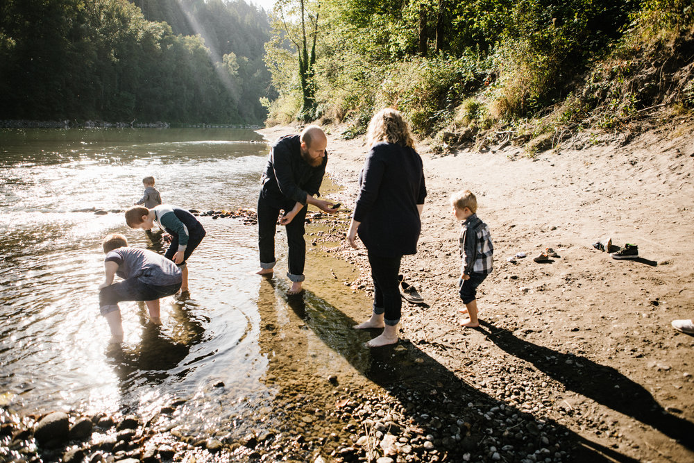 Young family of six collecting rocks by river