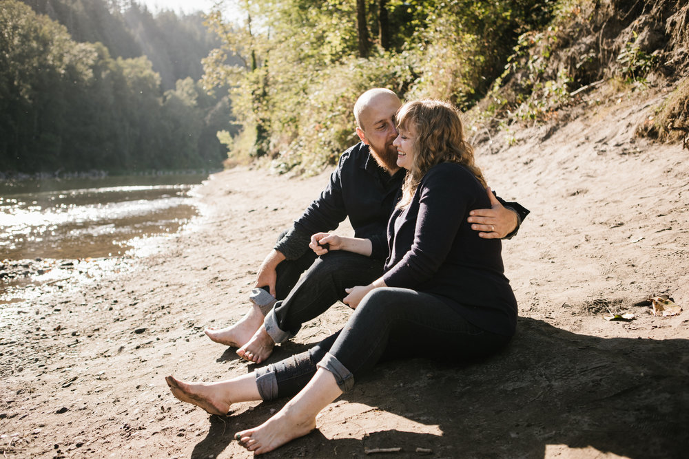 Husband and wife sitting by river
